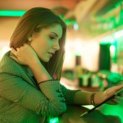young woman reading facebook on a digital tablet in cafe